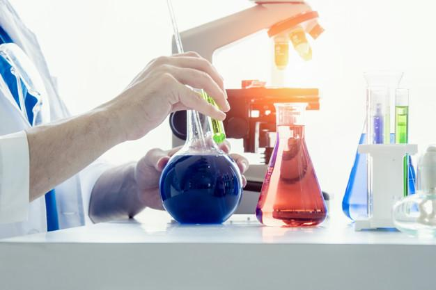Scientist or medical in lab coat holding test tube , Laboratory glassware containing chemical liquid
